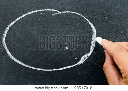 Man hold white chalk to write something on black board with circle background (Concept for business or education by have space to add text)