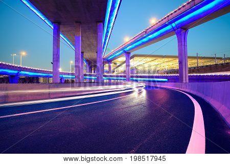 Empty Road Floor With City Viaduct Bridge Of Neon Lights Night