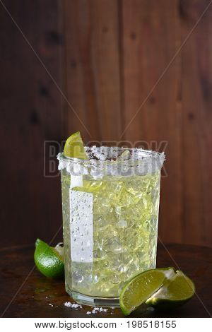 A margarita on the rocks in a glass tumbler. The rim of the glass is encrusted in salt and sliced limes are on the bar surface.