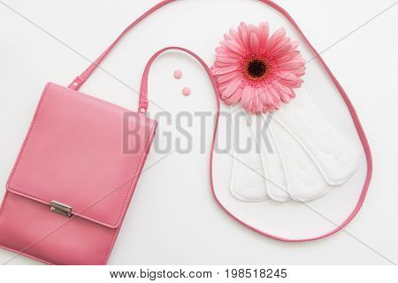 Contraceptive pills, white soft daily pads and flower with female pink bag, flat lay. Woman health, hormonal balance concept