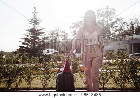 Portrait of an attractive young woman walking with a suitcase in a city street