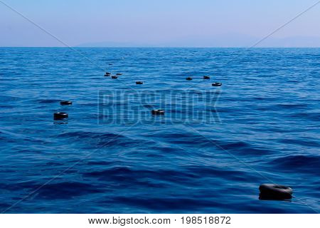 Inner tubes of car tires and life vests floating in the Mediterranean sea, used by a boat of refugees for flotation