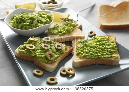 Bowl and delicious toasts with avocado and olives on platter