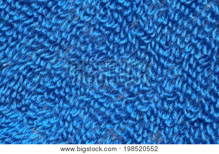 Macro shot of a blue towel. Texture is similar to the texture of a fleecy knotted-pile carpet. Geometric pattern of villi on fabric material. Diagonal pattern