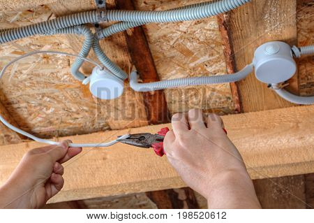 Installation of electrical wiring in the ceiling electrician hands with pliers close up.