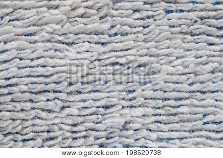 Macro shot of a white towel. Texture is similar to the texture of a fleecy knotted-pile carpet. Geometric pattern of villi on fabric material. White villi on a blue base