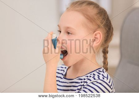 Girl using inhaler during asthmatic attack at home