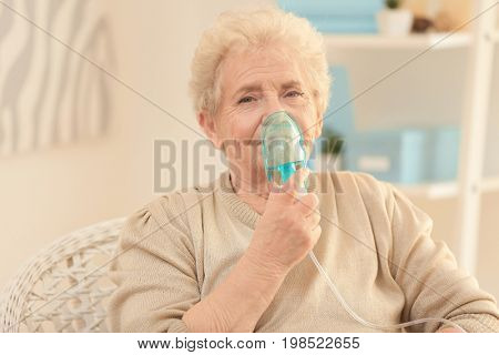 Elderly woman using asthma machine at home
