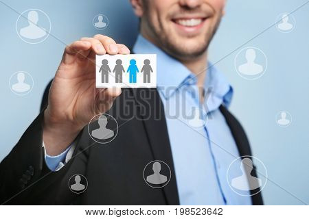 Young man holding business card on blue background. Concept of human resources management