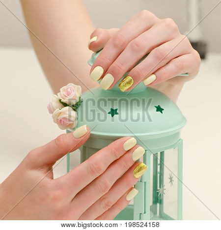 Beautiful Female Hands With A Manicure And A Lamp-candlestick On A Light Background. Yellow With Gol