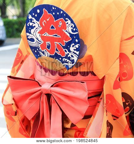 KYOTO, JAPAN - AUGUST 4, 2015 : Close-up shot of Japanese Yukata with a hand fan in summer festival. Japanese text translation is