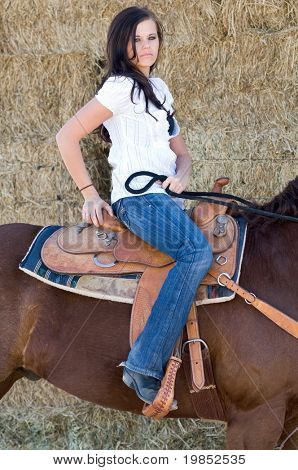 Young woman is seated in a saddle on her chestnut horse poster