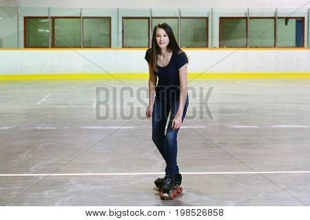 female teen doing t stop on quad roller skates