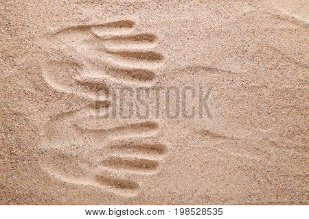 The two handprints on the beach sand