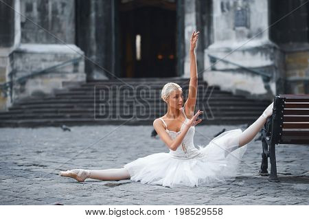 Horizontal shot of a beautiful ballerina performing in the city center outdoors doing splits near the bench stretching flexibility balance beauty athletics urban fashion grace concept.