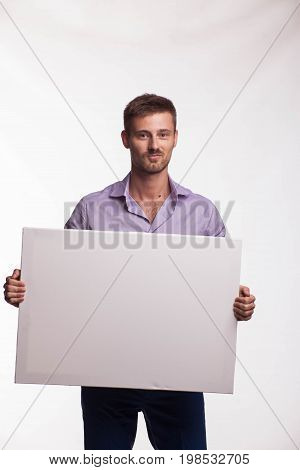 Young glad man portrait of a confident businessman showing presentation, pointing paper placard gray background. Ideal for banners, registration forms, presentation, landings, presenting concept.