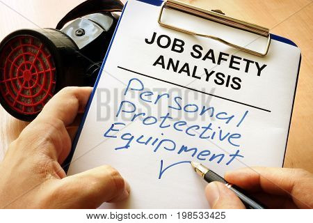 Man is writing words Personal protective equipment (PPE).