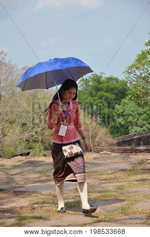 Laos Woman Guided Tour Walking And Hold Umbrella At Archaeological Site At Vat Phou Or Wat Phu