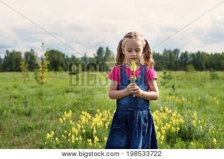 Little girl with a flower and her eyes closed standing in a summer field in a meditative pose.