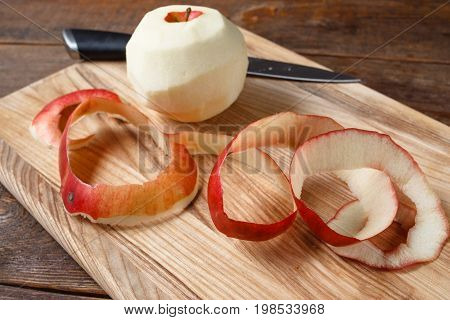 Single red apple paring by knife. Close up fresh fruit lay on wooden desk. Healthy food, dietary, cooking concept