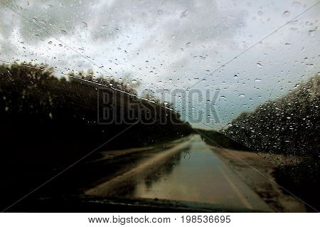 The windshield of the car during the rain is covered with water drops.
