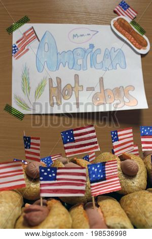 American hot dogs with American flags close plan, bun and sausage and an inscription american hot dogs on paper