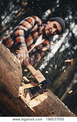 Serious Lumberjack In A Plaid Shirt And Hat Is Chopping A Big Tree With An Ax