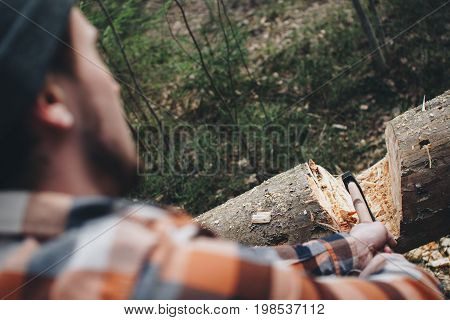 Woodcutter In A Plaid Shirt Posing With An Ax In Hands In The Woods