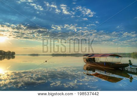 Sun rises over beautiful lake. Clouds are reflected in the water. HDR image.