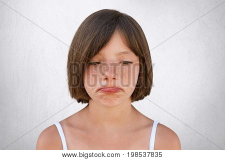 Little Upset Girl With Freckled Skin And Bobbed Hair, Curving Her Lips With Sorrorful Expression Bei
