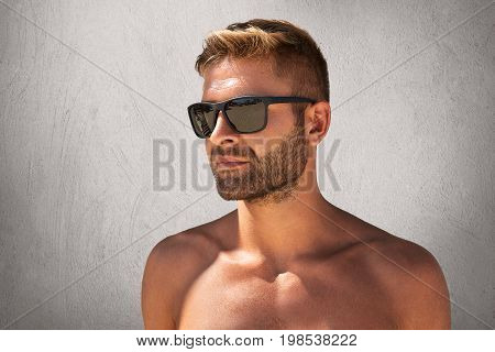 Strong Macho Man With Stylish Hairdo, Bristle, Posing Naked Against Grey Concrete Wall, Wearing Tren