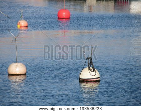Lots of mooring buoys floating on calm sea water