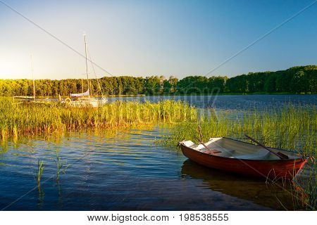 Rowing boat and sailboats floating over the Lake Lasmiady waters early morning. Masuria Poland.
