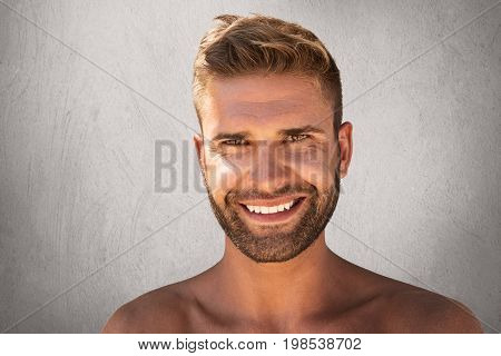 Positive Young Macho With Stylish Hairdo, Hazel Eyes, Bristle And Pleasant Smile, Demonstrating His