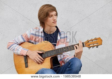 Talented Teenage Boy With Trendy Hairdo Wearing Shirt And Jeans Holding Acoustic Guitar Playing His