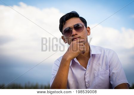 Man wearing glasses sitting on a pier