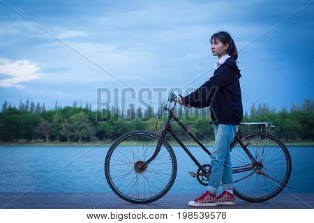 Young Woman Riding An Old Bicycle While Sunset.