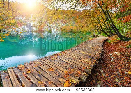 Famous tourist wooden pathway in the colorful deep forest with clean lake Plitvice National Park Croatia Europe