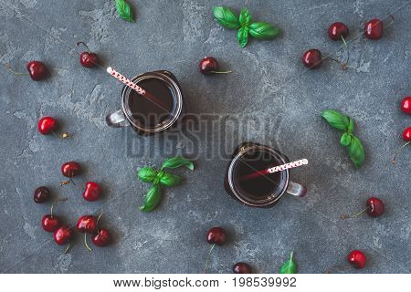 Cherry juice and fresh cherries on black background. Top view flat lay