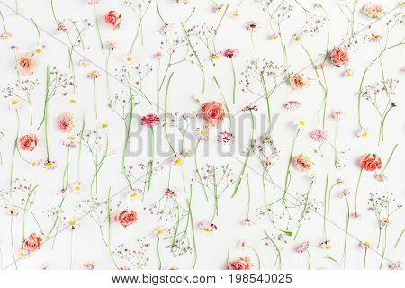 Pattern made of orange rose flowers pink gypsophila flowers and daisy flowers on white background. Flat lay top view
