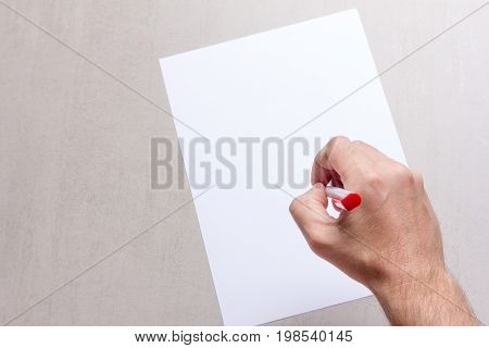 Mans hand with a ballpoint pen and blank white sheet of paper on a gray background top view close-up. mock up for text congratulations phrases lettering