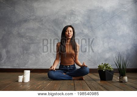 People meditation and relaxation. Attractive brunette Korean girl wearing top and jeans sitting on wooden floor in half lotus pose surrounded with candles and plant-pots meditating with eyes closed