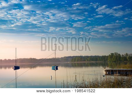 Yachts float on the calm waters of the lake. Early morning. Masuria Poland .