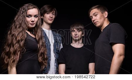 Young rock musicians - woman and men on black background