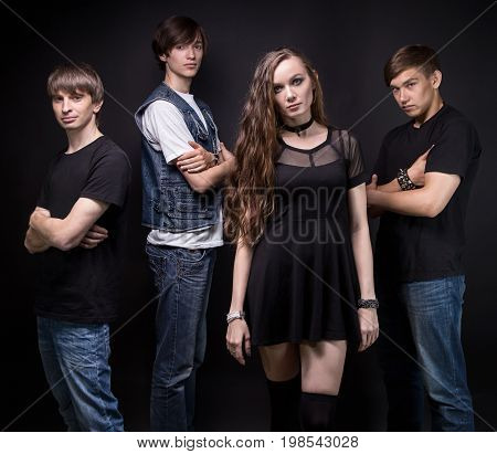 Rock band - young woman and men on black background