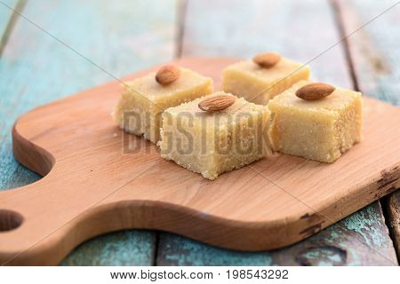 Homemade tasty semolina halva with whole almonds cut in squares on wooden board. Traditional Indian sweets closeup