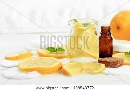 Refreshing lemon water facial tonic. Yellow citrus slices in jar, white cotton pads. Home beauty care remedies.