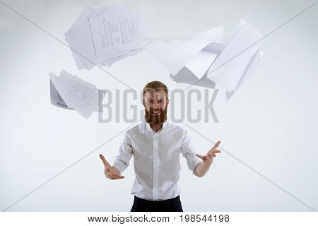 People business job profession and occupation. Stressed pissed-off young bearded office worker in formal wear having furious look throwing paper sheets up in the air after he failed project