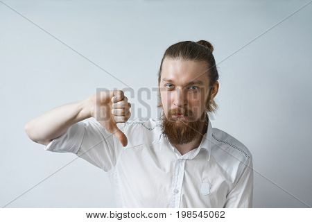 Pessimistic young businessman with thick beard and hair bun wearing formal shirt having upset and disappointed look showing thumbs down expressing disapproval of offer or situation. Body language