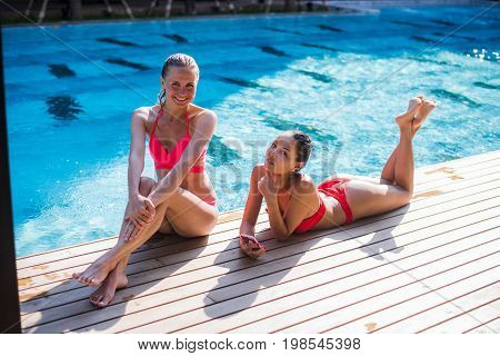 Two attractive blonde and brunette girls with long hair are lying on flor near pool. They wear bikini and swimsuit. They are looking to the different sides. View from above